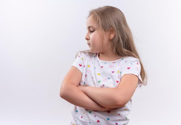 Regardant à côté petite écolière portant un t-shirt blanc croisant les mains sur un mur blanc isolé