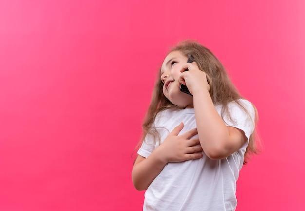 Regardant à côté petite écolière portant un t-shirt blanc parle au téléphone sur un mur rose isolé