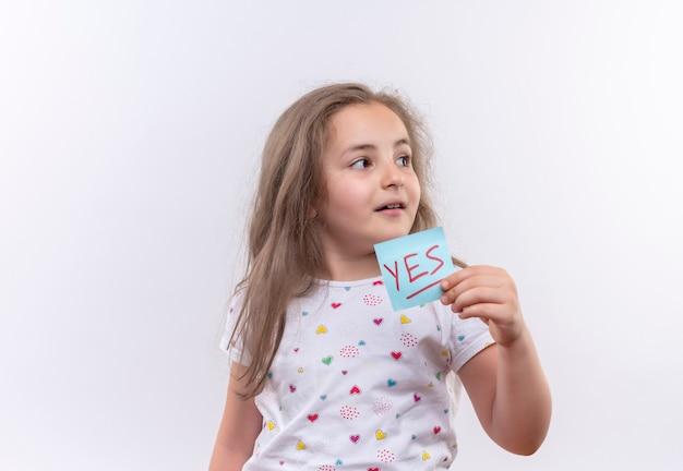 Regardant à côté petite écolière portant un t-shirt blanc tenant une marque de papier sur un mur blanc isolé