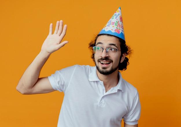 Regardant le côté souriant bel homme portant des lunettes et une casquette d'anniversaire soulevant la main isolé sur fond orange