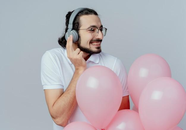 Regardant côté souriant bel homme portant des lunettes et des écouteurs tenant des ballons