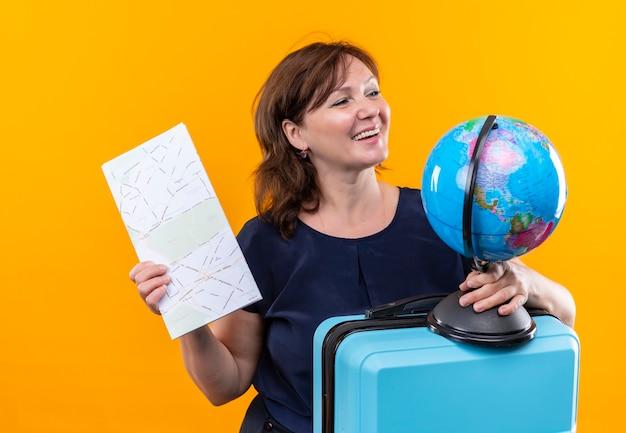 Regardant à côté souriant voyageur d'âge moyen woman holding valise et globe avec carte sur mur jaune isolé