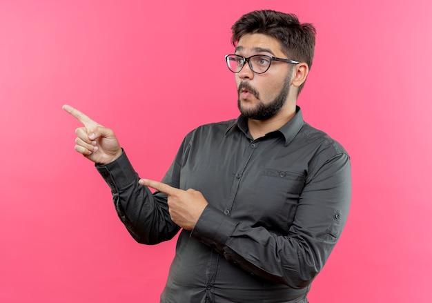 Regardant le côté surpris jeune homme d'affaires portant des lunettes points sur le côté