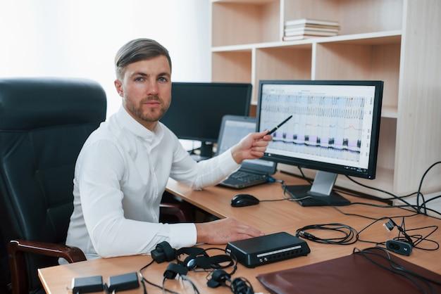 Regardant dans la caméra. l'examinateur polygraphique travaille dans le bureau avec l'équipement de son détecteur de mensonge
