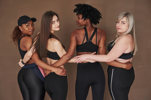 Regardant derrière la caméra. groupe de femmes multiethniques debout contre l'espace brun