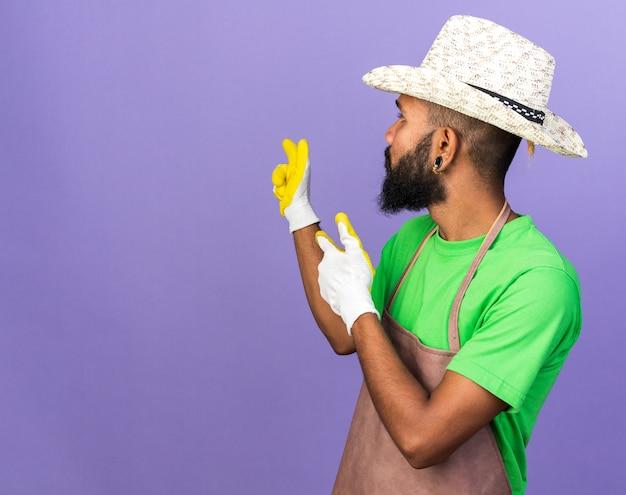 Regardant derrière un jeune jardinier afro-américain portant un chapeau de jardinage avec des gants pointe derrière isolé sur un mur bleu avec espace pour copie