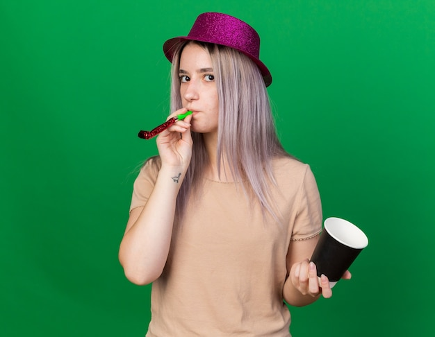 En regardant devant une belle jeune femme portant un chapeau de fête soufflant un sifflet de fête tenant une tasse de café isolée sur un mur vert