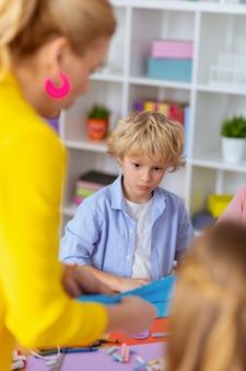 En regardant l'enseignant. écolier aux cheveux blonds mignon regardant l'enseignant faisant l'ornement appliqué