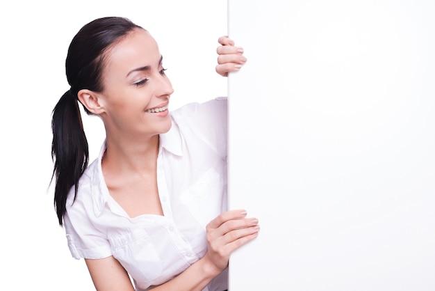 En regardant l'espace de copie. belle jeune femme regardant l'espace de copie et le pointant tout en isolé sur blanc