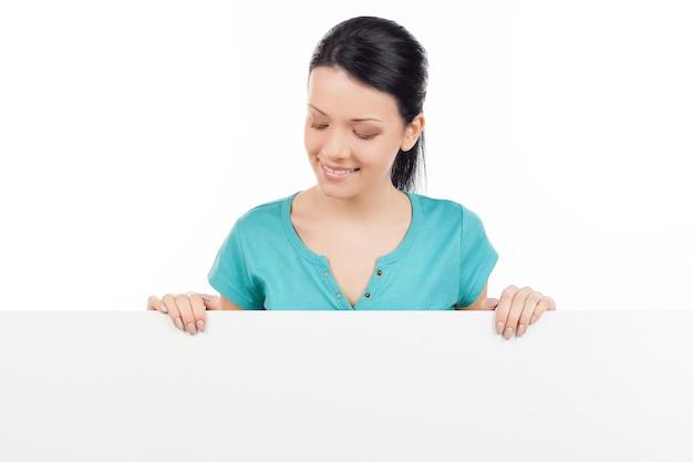 En regardant l'espace de copie. belle jeune femme se penchant sur l'espace de copie et le regardant tout en isolé sur blanc