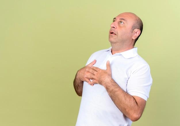 Regardant l'homme mûr surpris mettant les mains ensemble sur la poitrine