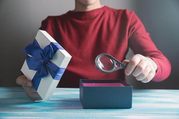 Regardant à l'intérieur d'un cadeau avec une loupe