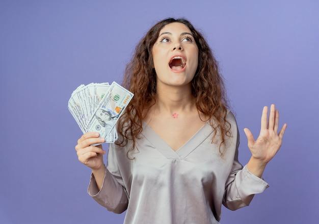 Regardant joyeuse jeune jolie fille tenant de l'argent et levant la main