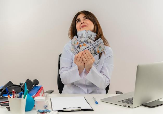 Regardant jusqu'à heureux femme médecin d'âge moyen portant portant une robe médicale avec stéthoscope assis au bureau de travail sur un ordinateur portable avec des outils médicaux tenant de l'argent sur un mur blanc avec espace de copie