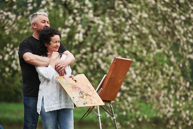 Regardant loin. couple d'âge mûr ont des journées de loisirs et travaillent ensemble sur la peinture dans le parc