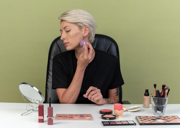 En regardant le miroir, une belle jeune fille est assise à table avec des outils de maquillage appliquant une crème tonifiante avec une éponge isolée sur un mur vert olive