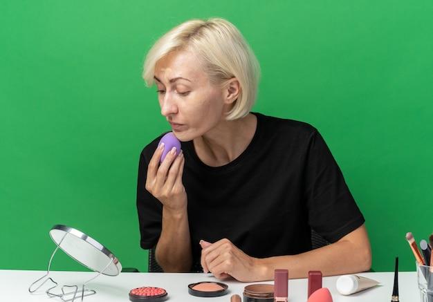 En regardant le miroir, une belle jeune fille est assise à table avec des outils de maquillage appliquant une crème tonifiante avec une éponge isolée sur un mur vert