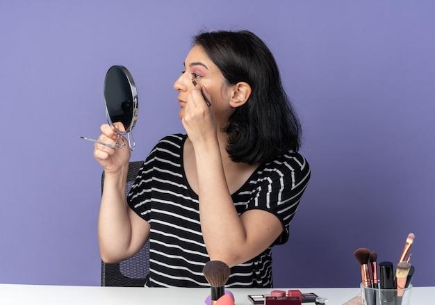 En regardant le miroir, une belle jeune fille est assise à table avec des outils de maquillage, dessine une flèche avec un eye-liner isolé sur un mur bleu