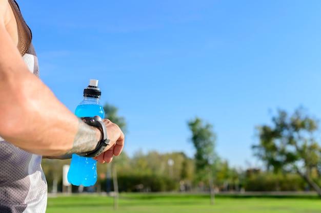 Regardant une montre de sport intelligente dans le parc avec une boisson isotonique