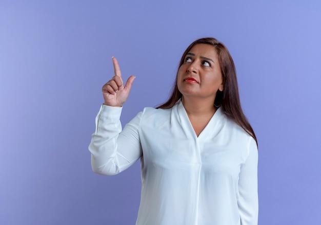 Regardant la pensée de la femme d'âge moyen caucasienne occasionnelle pointe vers le haut