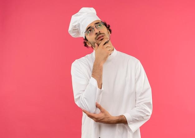 Regardant la pensée de jeune homme cuisinier portant l'uniforme de chef et lunettes mettant la main sur le menton