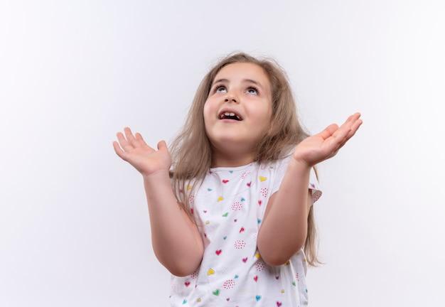 Regardant la petite écolière portant un t-shirt blanc montrant le geste de prier sur fond blanc isolé