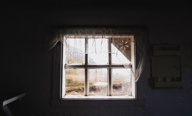 Regardant à travers une vieille fenêtre cassée