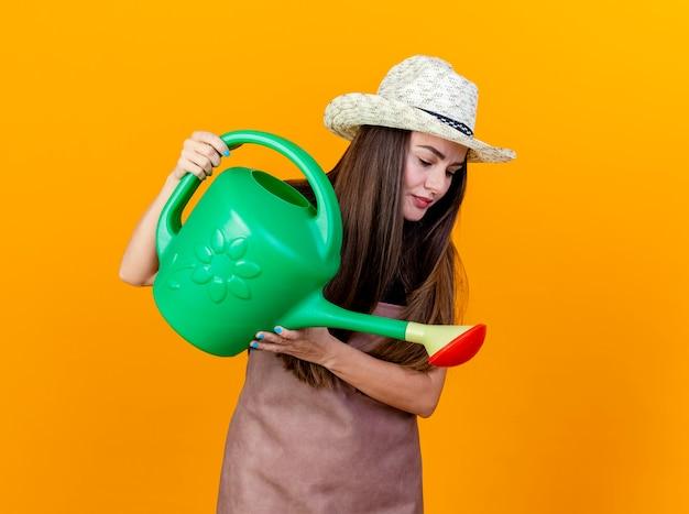 Regardant vers le bas belle fille de jardinier en uniforme et chapeau de jardinage arrosage avec arrosoir isolé sur fond orange