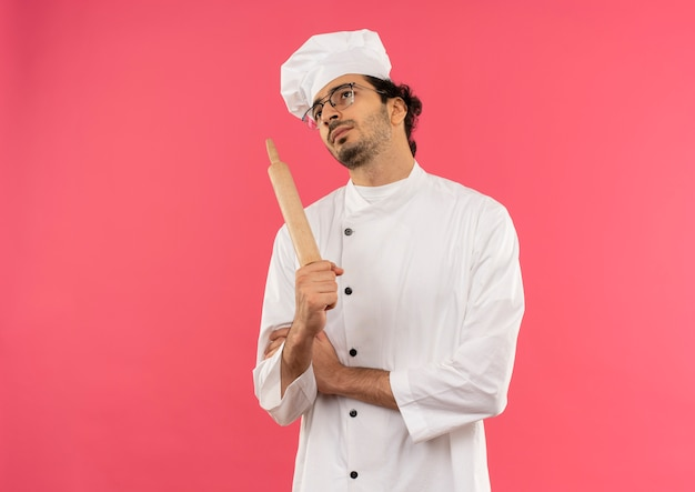 Regardant vers le haut de la pensée jeune cuisinier mâle portant l'uniforme de chef et des lunettes tenant une poêle à rouler