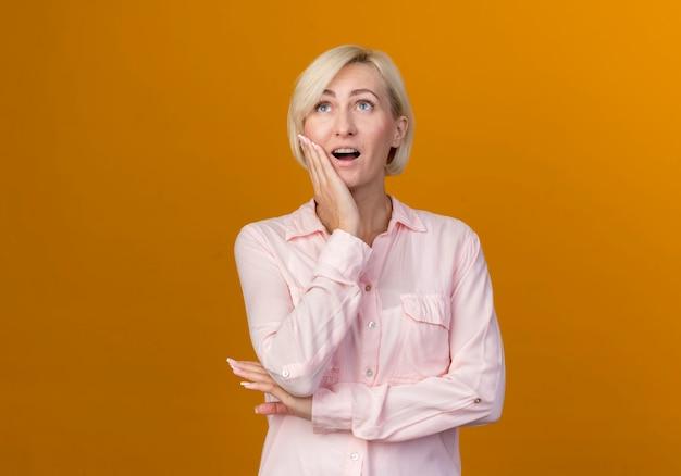 Regardant vers le haut surpris jeune femme slave blonde mettant la main sur la joue isolé sur mur orange