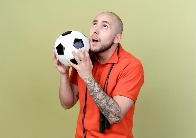 Regardant vers le haut surpris jeune homme sportif avec corde à sauter sur l'épaule tenant le ballon