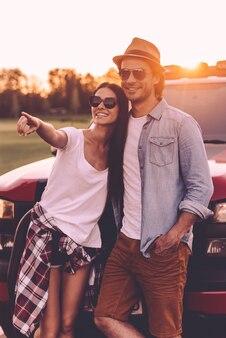 Regarde là-bas! beau jeune couple se liant les uns aux autres et s'appuyant sur leur camionnette tandis qu'une femme pointe du doigt et sourit