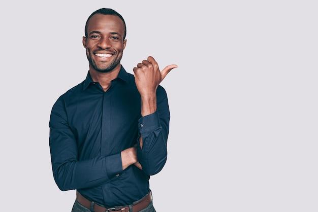 Regarde là-bas! beau jeune homme africain pointant du doigt et vous souriant en se tenant debout