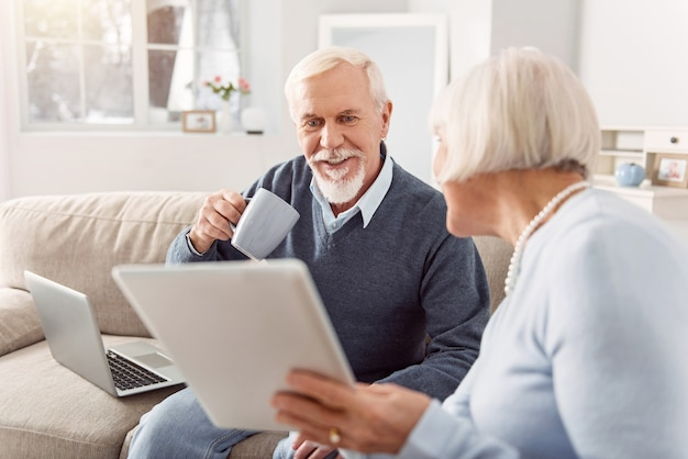 Regarde. bel homme âgé de boire du café et de lire l'article sur la tablette que sa femme lui montre alors qu'il était assis sur le canapé