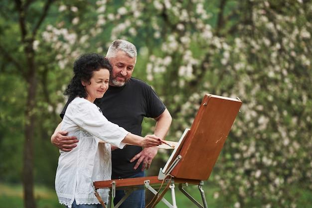 Regarde ça. couple d'âge mûr ont des journées de loisirs et travaillent ensemble sur la peinture dans le parc