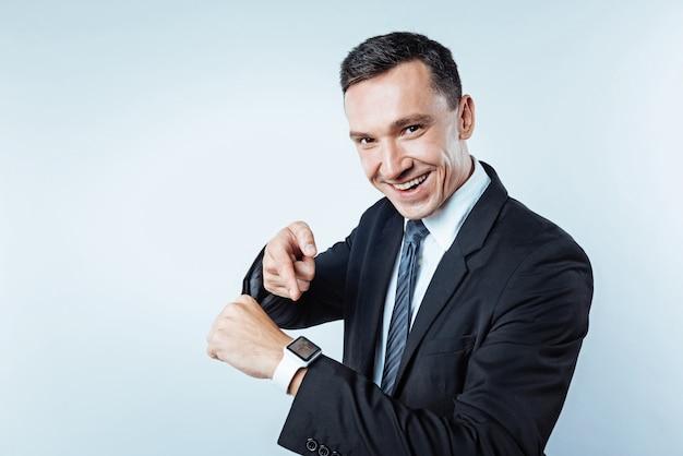 Regarde ça. entrepreneur mature regardant la caméra avec un large sourire sur son visage tout en montrant sa montre-bracelet innovante sur l'arrière-plan.