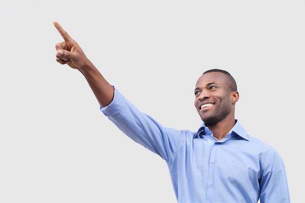 Regarde ça! gai jeune homme noir pointant du doigt et souriant tout en se tenant isolé sur fond gris