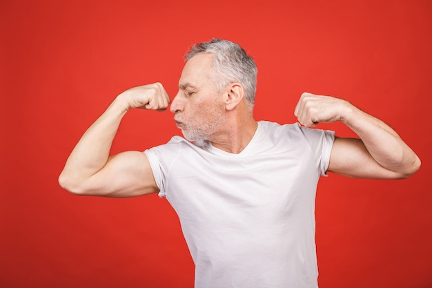 Regarde ça! homme senior montrant le muscle. homme âgé fléchissant ses bras isolés. joyeux excité papy retraité cool moderne pratiquant la musculation.