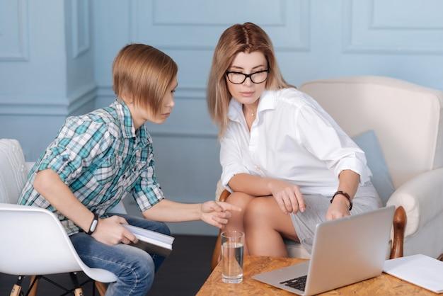 Regarde. élégant jeune homme portant une chemise à carreaux et un jean tenant un livre dans la main droite tout en pointant sur un ordinateur portable