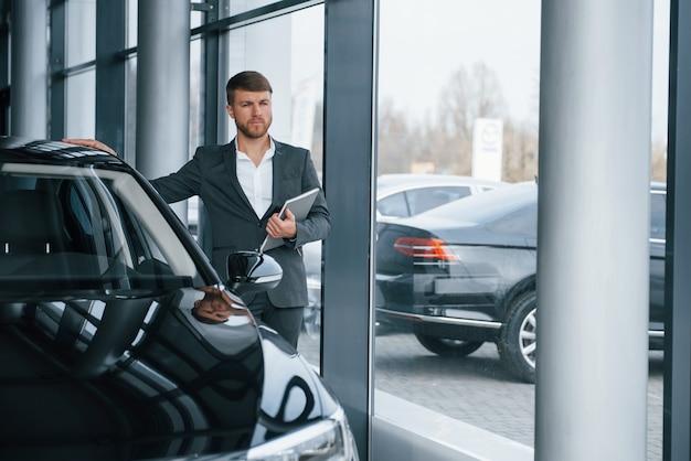 Regarde loin. homme d'affaires barbu élégant et moderne dans le salon automobile