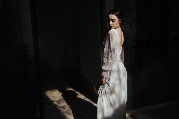 Regarder en arrière avec une belle expression en écoutant une robe blanche