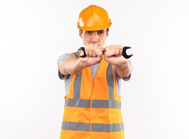 Regarder la caméra jeune homme constructeur en uniforme tenant une clé à fourche