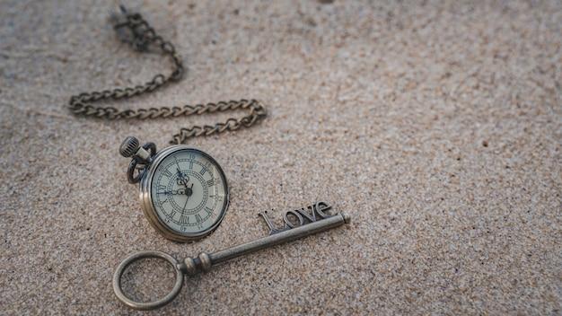 Regarder le collier et la clé sur la plage de la mer