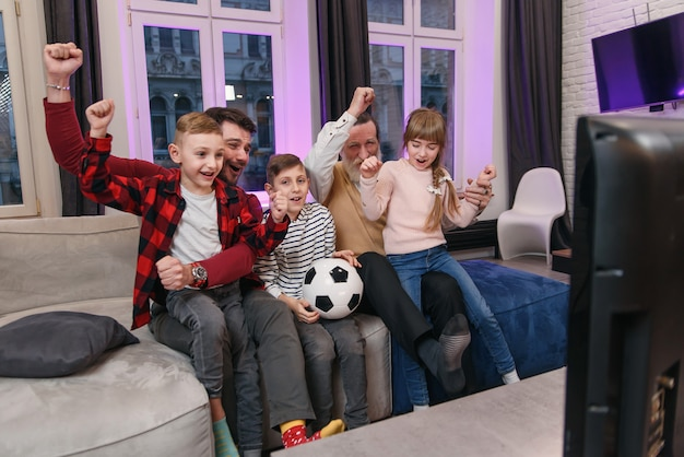 Regarder la famille match de football américain, championnat sur le canapé à la maison. les fans encouragent émotionnellement l'équipe nationale préférée. enfants avec père et grand-père profitant des loisirs à la maison.