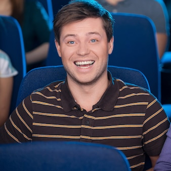 Regarder un film ensemble. heureux jeune couple mangeant du pop-corn et buvant du soda en regardant un film au cinéma