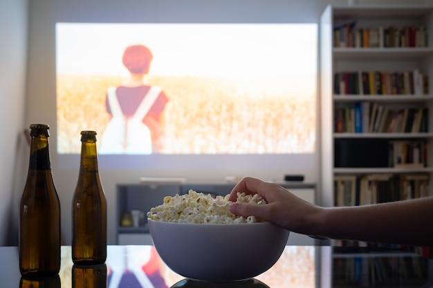 Regarder un film à partir d'un vidéoprojecteur dans une pièce.