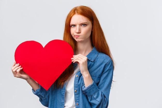 Regarder sérieusement troublé, incertain jolie fille rousse pensant quel cadeau acheter en plus de la saint-valentin
