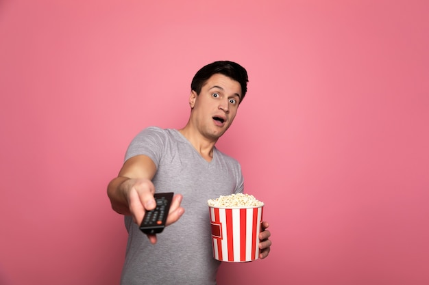 Regarder la télé. homme surpris, qui tient une télécommande dans sa main droite et un tube de pop-corn dans sa main gauche et regarde dans la caméra