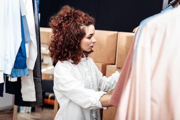 Regarder des vêtements. jeune femme bouclée attrayante regardant des vêtements dans la boutique le week-end