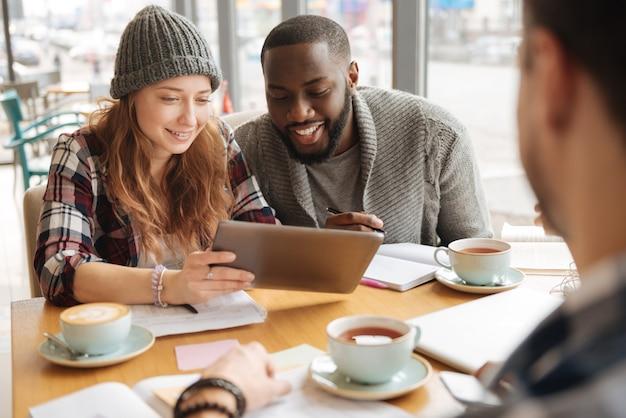 Regarder des vidéos amusantes. belle jolie femme tenant une tablette moderne et partageant des informations avec son camarade pendant le processus d'étude au café.